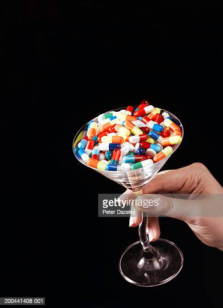 Woman holding martini glass filled with pills, close-up