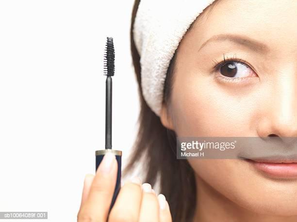 Woman holding mascara brush next to face, studio shot, close up