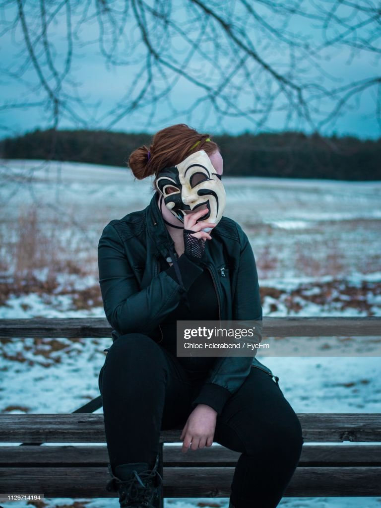 Woman Holding Mask Over Face While Sitting On Bench : Stock Photo
