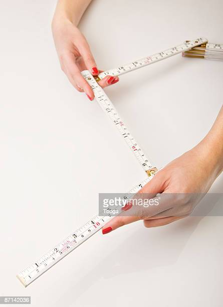 woman holding measuring stick - ruler stock photos and pictures