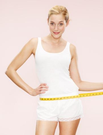 woman holding measuring tape around waist - gettyimageskorea