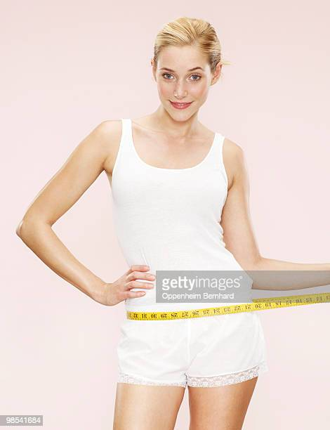 woman holding measuring tape around waist