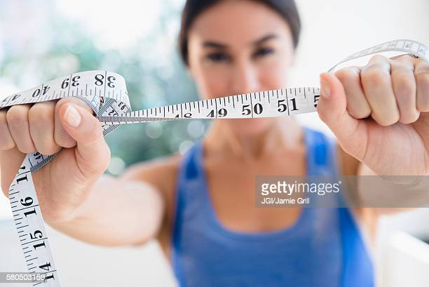 woman holding measuring tape - waist stock pictures, royalty-free photos & images
