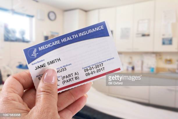 femme tenant la carte d'assurance maladie en cabinet médical - medicare photos et images de collection