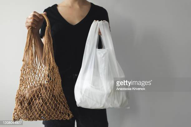 woman holding mesh eco bag shopper and plastic shopping bags. what you choose: plastic bags or multi-use eco bags. zero waste concept with copy space. - ビニール袋 ストックフォトと画像