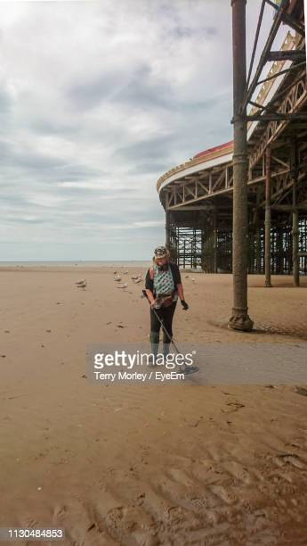 woman holding metal detector while walking at beach against cloudy sky - metal detector stock photos and pictures