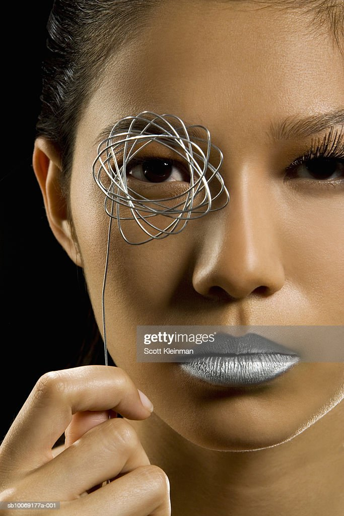 Woman holding metal star shape by eye, studio portrait : Stockfoto
