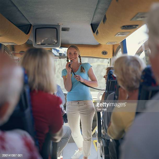 Woman holding microphone on bus with passengers (focus on woman)