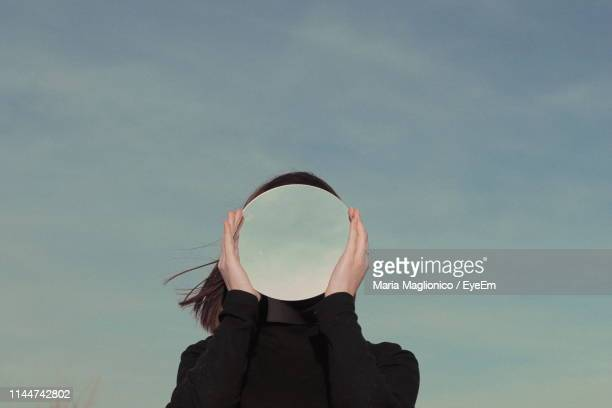 woman holding mirror against sky - obscured face stock pictures, royalty-free photos & images