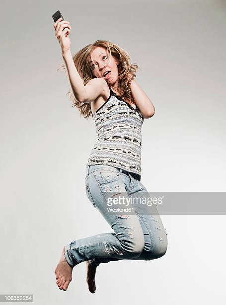 Woman holding mobile phone and jumping