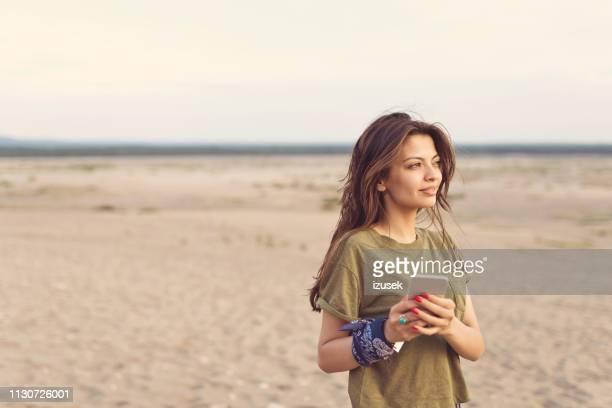 vrouw holding mobiele telefoon in de woestijn - izusek stockfoto's en -beelden