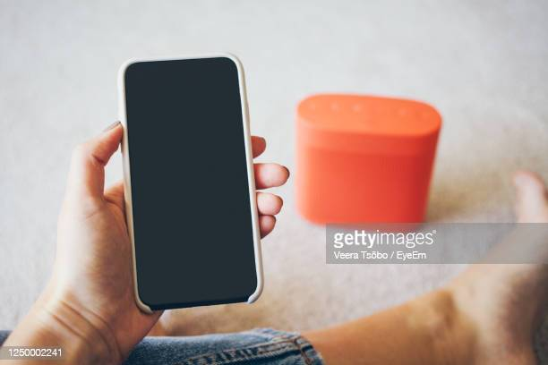 woman holding mobile phone in home - bluetooth stock pictures, royalty-free photos & images