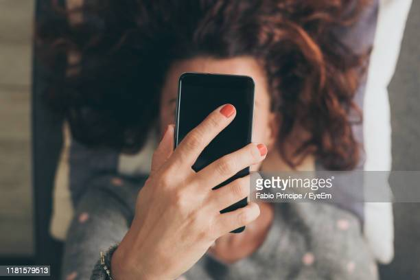woman holding mobile phone over face while lying on sofa - obscured face stock pictures, royalty-free photos & images