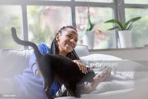 woman holding mobile phone stroking cat - florence douillet photos et images de collection