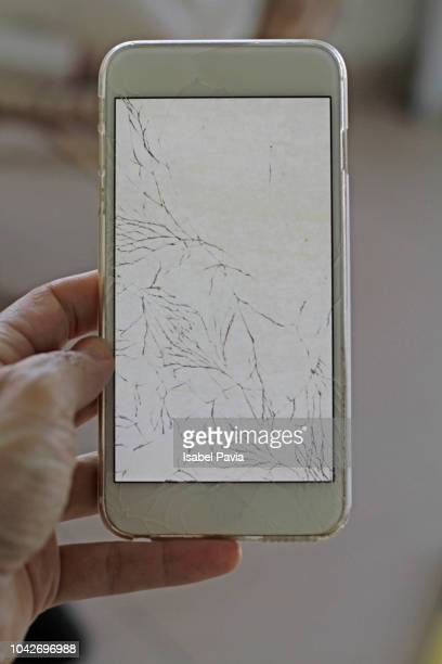 Woman Holding Mobile Phone With Broken Screen