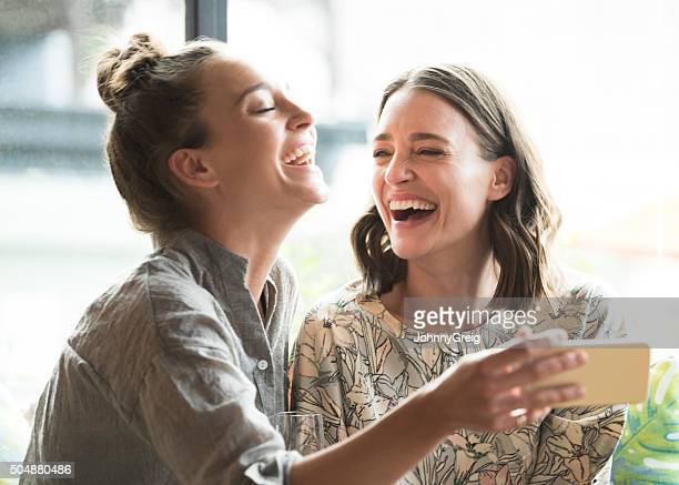 woman holding mobile phone with freind, laughing - mid adult women stock pictures, royalty-free photos & images