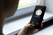 woman holding mobile phone with incoming call from unknown caller