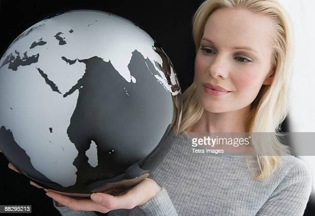 Woman holding modern globe