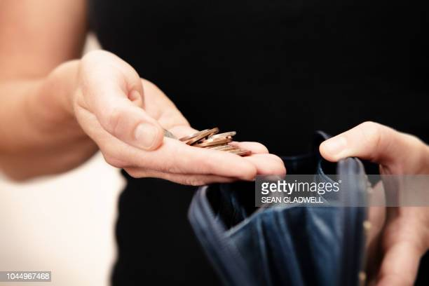 woman holding money over purse - armoede stockfoto's en -beelden