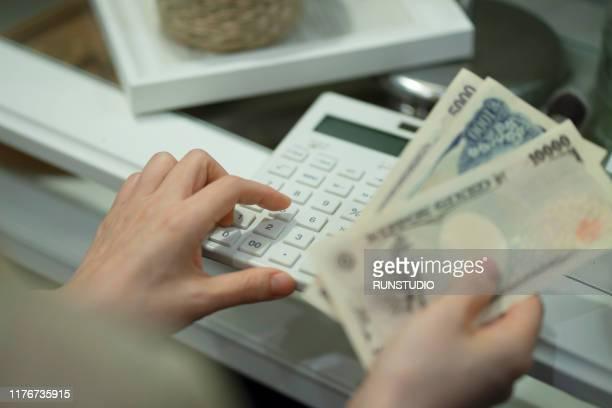 woman holding money with calculator - 税金 ストックフォトと画像