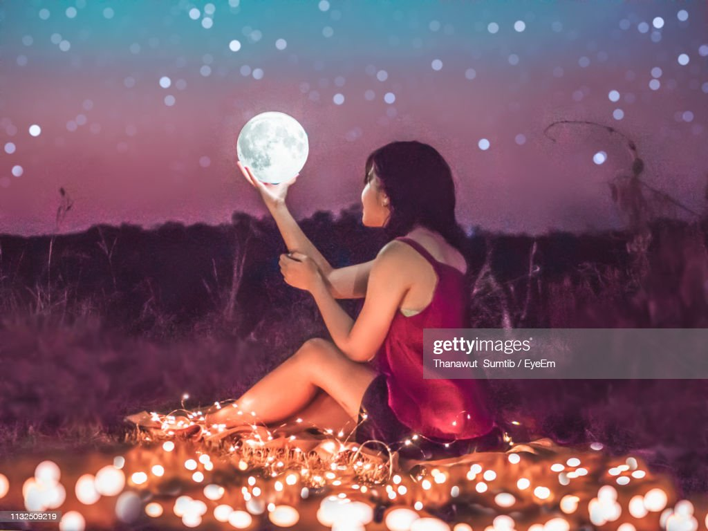 Woman Holding Moon While Sitting On Field : Stock Photo