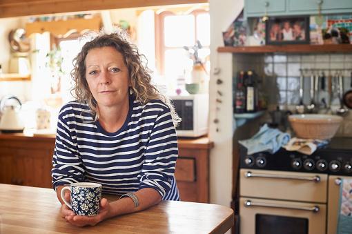 Woman holding mug of tea - gettyimageskorea