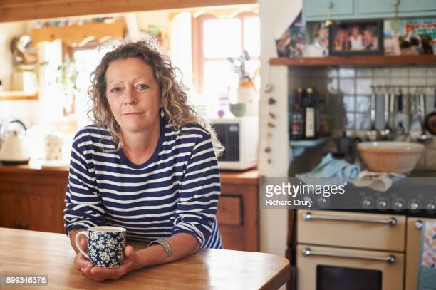 woman holding mug of tea - serious stock pictures, royalty-free photos & images
