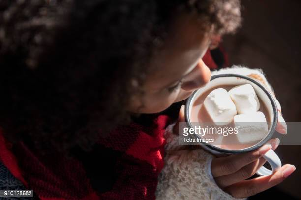 woman holding mug with hot chocolate and marshmallows - hot chocolate stock pictures, royalty-free photos & images
