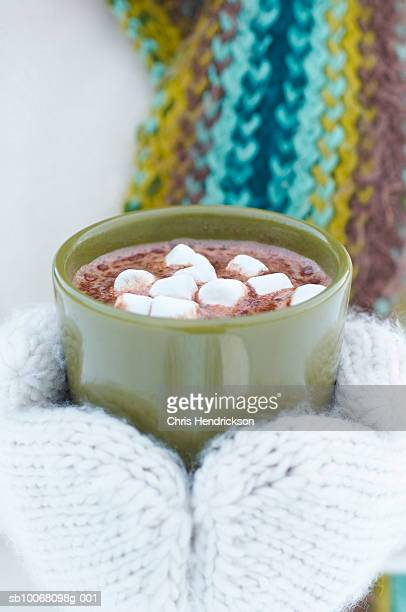 Woman holding mug with hot chocolate with marshmallows, close up, mid section