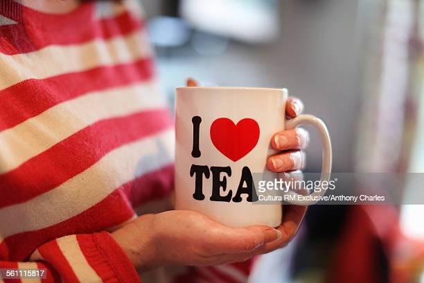 Woman holding mug with I heart tea, cropped