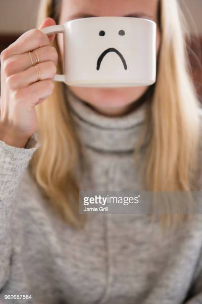 Woman holding mug with sad face in front of face