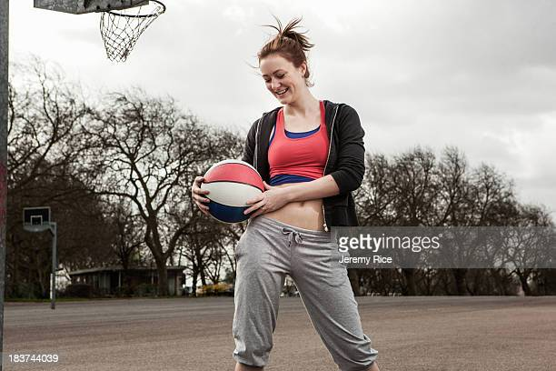 Woman holding netball to waist