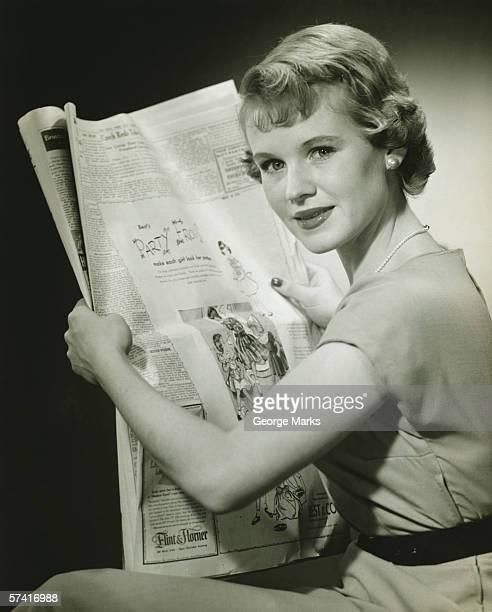 Woman holding newspaper, posing in studio, (B&W), (Portrait)
