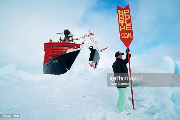 Woman Holding North Pole Sign