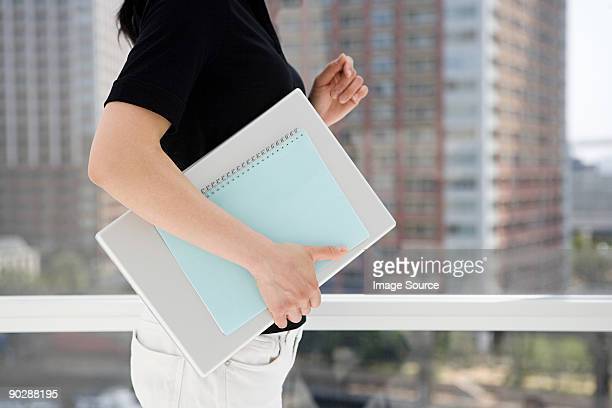 Woman holding notebook and documents