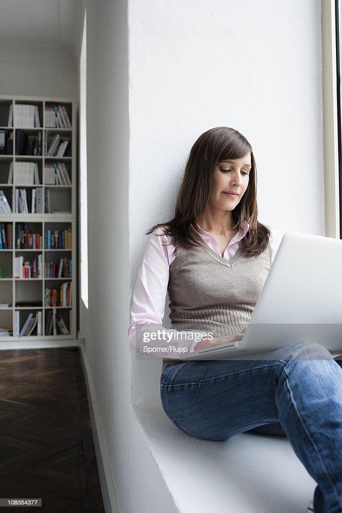 Woman holding notebook on lap : Stockfoto