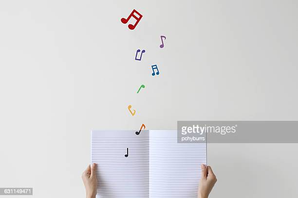 woman holding notebook with musical notes flying off page - musical note stock photos and pictures