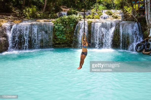 woman holding on to a rope over a waterfall, siquijor, philippines - filipino ethnicity and female not male fotografías e imágenes de stock