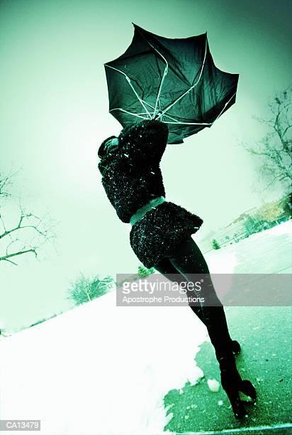 woman holding on to umbrella in snowstorm, rear view (green tone) - virada ao contrário - fotografias e filmes do acervo