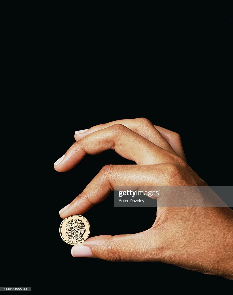 woman holding one pound coin ストックフォト getty images