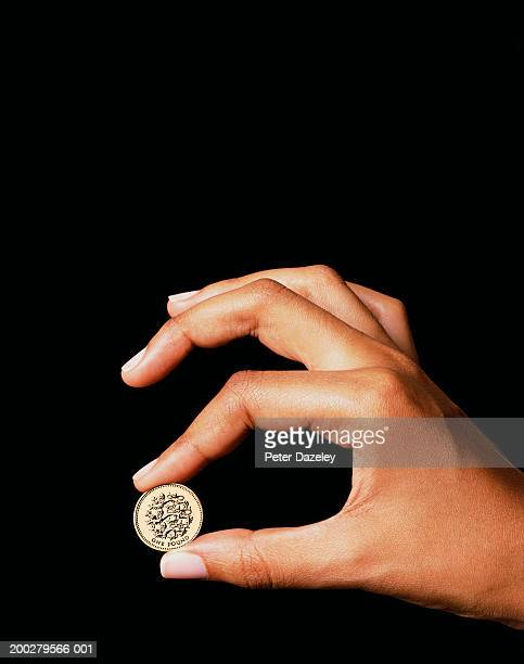 Woman holding one pound coin