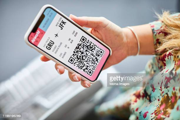 woman holding online boarding pass in cellphone - airplane ticket stock pictures, royalty-free photos & images