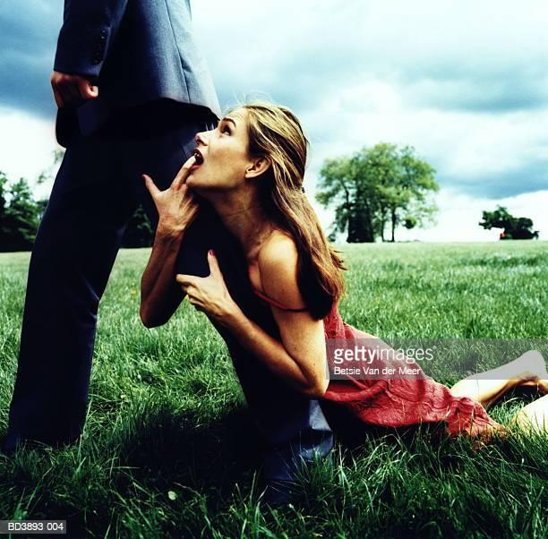 Woman holding onto man's leg, as he walks away