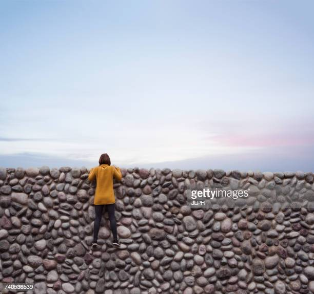 woman holding onto stone wall, looking over top - 見渡す ストックフォトと画像