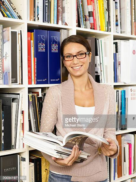 Woman holding open book by bookshelf, smiling, portrait