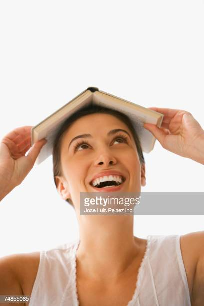 Woman holding open book on head