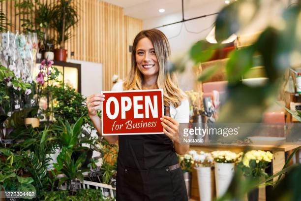 woman holding open for business sign in flower shop - store opening stock pictures, royalty-free photos & images