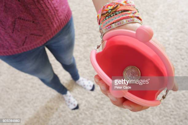 Woman holding open purse with a single one pound coin