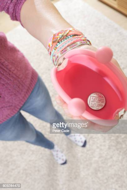 Woman holding open purse with one 5 pence coin