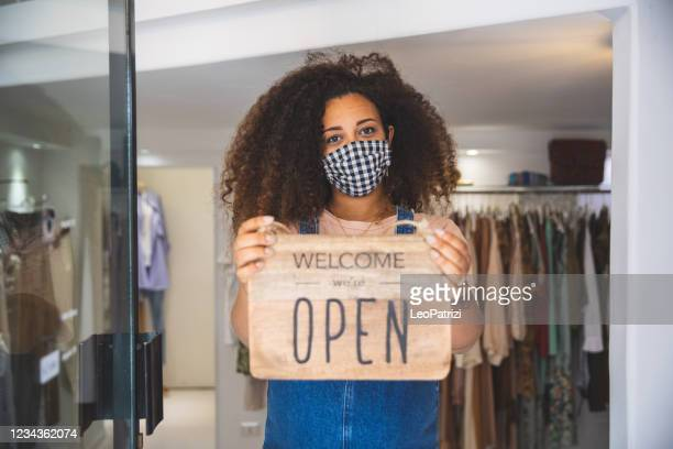 woman holding open sign in a small business boutique shop after covid-19 pandemic - reopening stock pictures, royalty-free photos & images